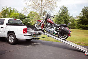 Automatic Loading System places motorcycle onto truckbed.
