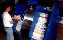 Feeder dispenses books onto flat conveyor.