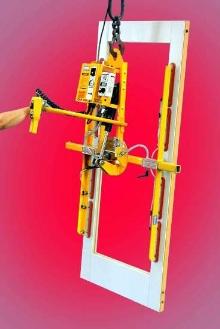 Vacuum Lifter unloads and reorients doors.