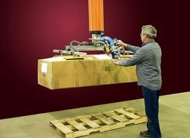 Vacuum Tube Lifter loads heavy cartons onto skids.